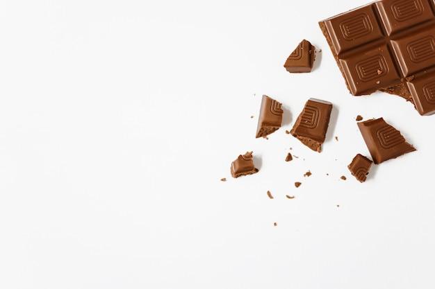 白い背景に壊れたチョコレートバー Premium写真
