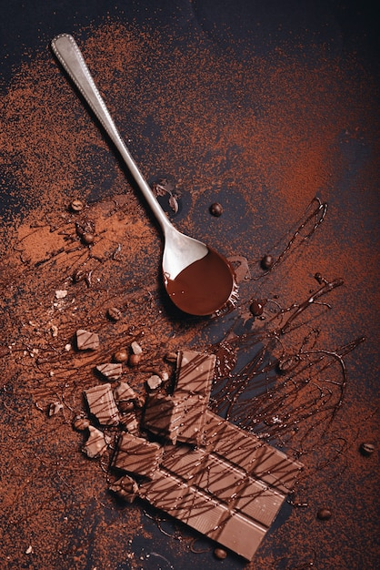 Broken chocolate bar and syrup on dusted coffee powder Free Photo