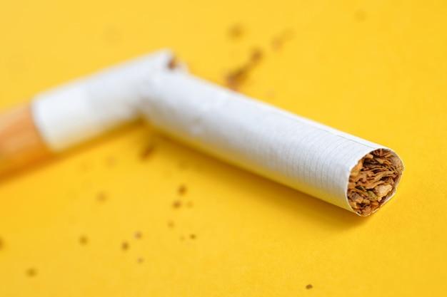 Broken cigarette in half on yellow Premium Photo