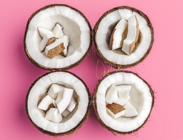 Broken coconut pieces on bright pink background, top view, copy space Premium Photo