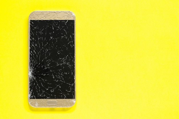 Broken cracks cell mobile phone on yellow background Premium Photo