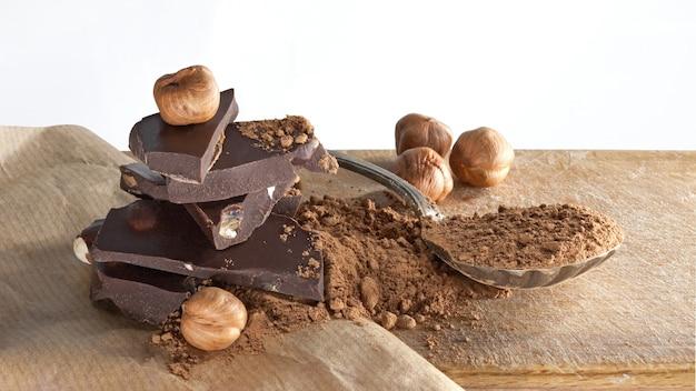 베이지 색 종이 표면에 깨진 다크 초콜릿 바, 코코아 가루 및 헤이즐넛. 클로즈업 샷 프리미엄 사진