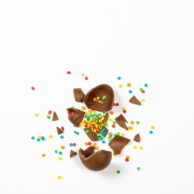 Broken easter chocolate egg and colorful decorations on a light surface. easter concept, easter treats. square. flat lay, top view Premium Photo