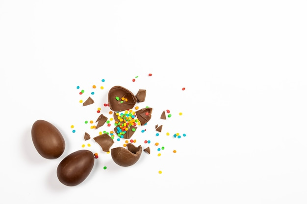 Broken easter chocolate eggs and colorful decorations on a light surface. easter concept, easter treats. flat lay, top view Premium Photo
