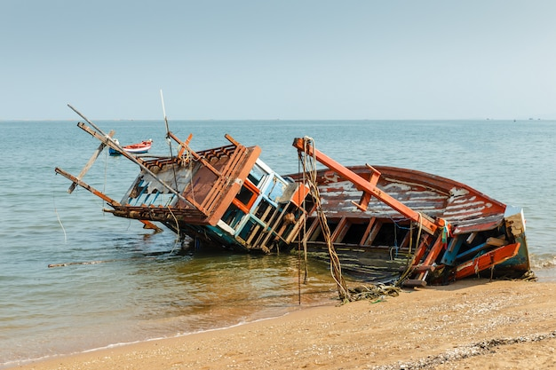 A broken fishing ship lies on its side near the shore, shipwrecked Premium Photo
