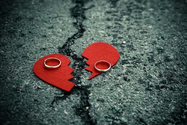 Broken heart with wedding rings on cracked asphalt Premium Photo