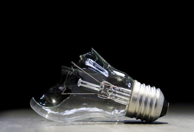 Broken lightbulb on stone floor, bad idea concept, solution background Premium Photo