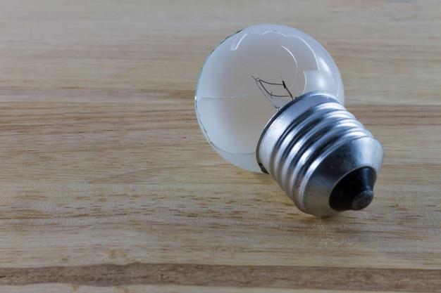 Broken lightbulb on the wood background Premium Photo