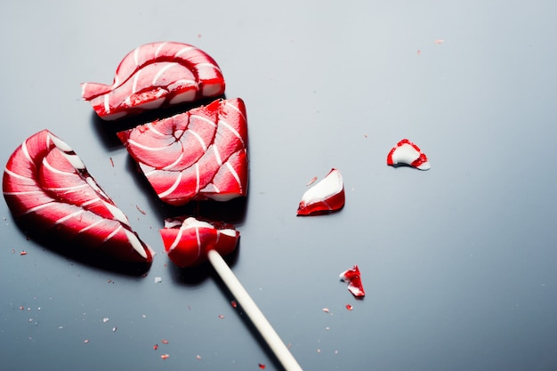 Broken lollipop in shape of heart on a dark background Premium Photo