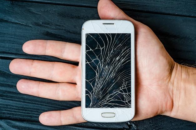 Broken phone screen in hand. broken glass of smartphone Premium Photo