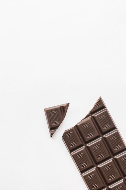 Broken piece of chocolate bar on white background Free Photo