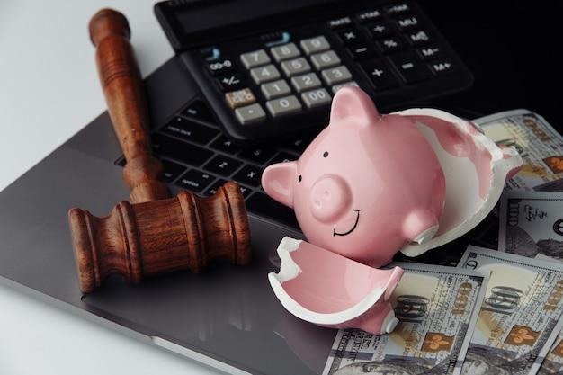 Сломанная копилка, наличные деньги и деревянный молоток на клавиатуре. концепция бизнеса и банкротства. Premium Фотографии