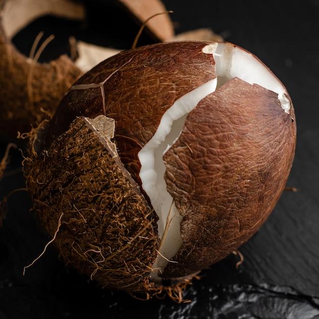 Broken raw coconut on black slate stone background. Premium Photo