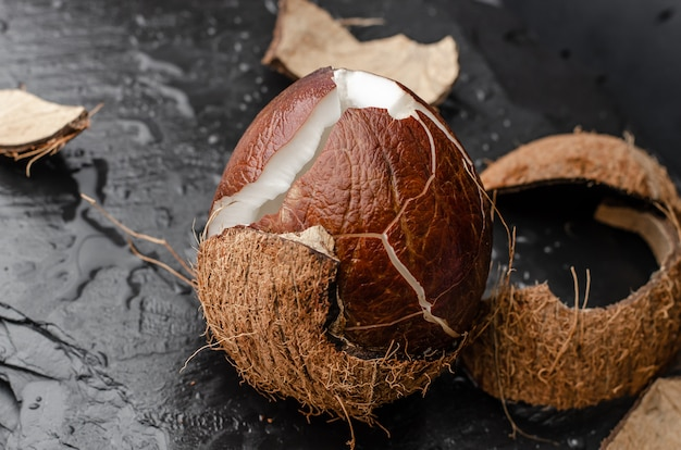 Broken ripe coconut on black slate stone Premium Photo