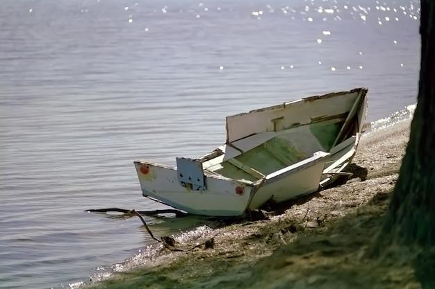 Piccola barca rotta parcheggiata sullo specchio d'acqua Foto Gratuite
