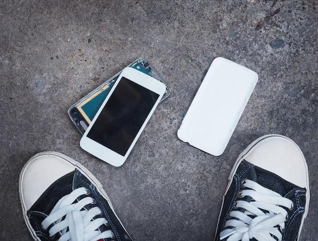 Broken smart phone on concrete floor between owner's sneaker shoes Premium Photo