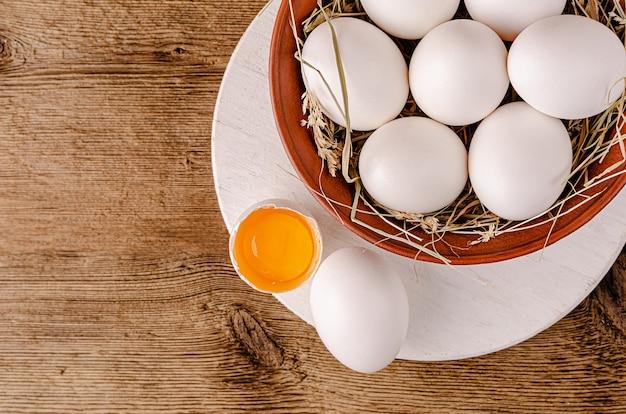 Разбитое белое яйцо с сырым желтком на деревянном фоне Premium Фотографии