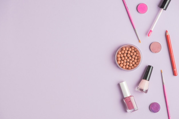 Bronzed pearls with cosmetics products on colored background Free Photo