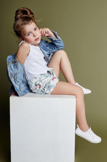 Brooding beautiful girl sitting on a white cube Premium Photo