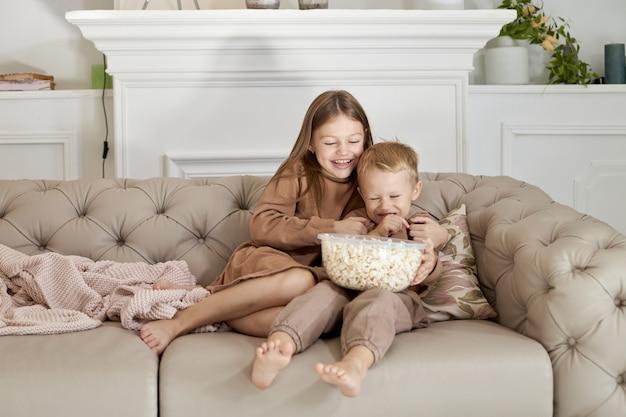 自宅のソファに座ってポップコーンを食べる兄と妹 Premium写真