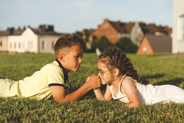 草の上に横たわる兄妹は腕相撲をしている。 Premium写真