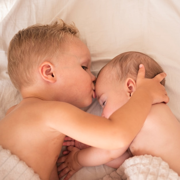 Brother kissing newborn baby on forehead Free Photo