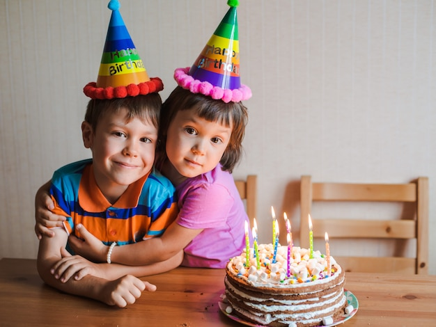 Brother And Sister Are Eating A Birthday Cake And Hugging Photo