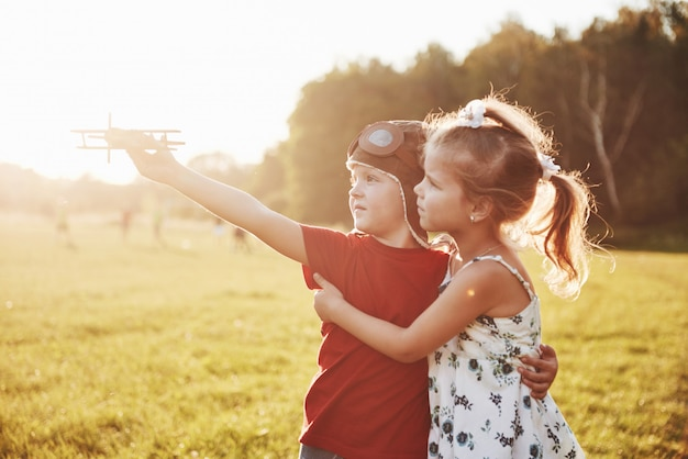 Brother and sister are playing together. two children playing with a wooden airplane outdoor Free Photo