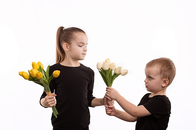 Brother and sister in black blouses holding tulips in their hands. Premium Photo