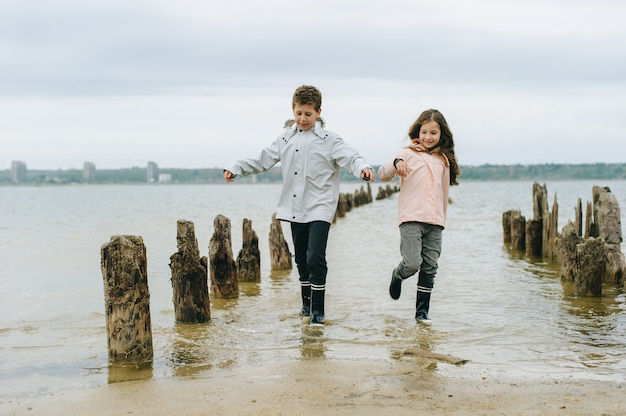 Brother and sister have a fun and playing near the sea Premium Photo