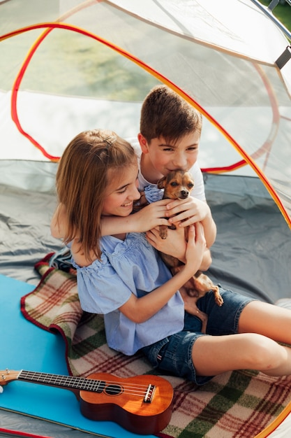 Brother and sister loving their pet sitting in tent Free Photo