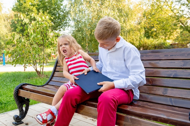Brother and sister in the park on a bench take away a laptop from each other Premium Photo