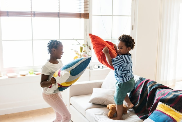 Brother and sister pillow fighting in living room Free Photo