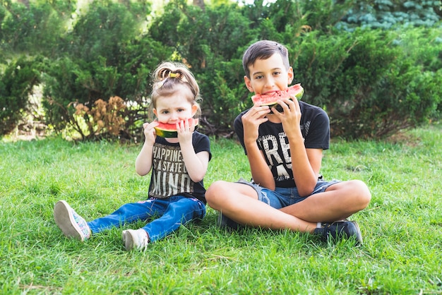 Brother and sister sitting in garden eating watermelon Free Photo