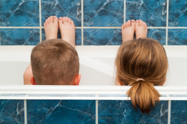 Brother and sister taking a bubble bath. little boy and girl playing. healthcare and hygiene concept. Premium Photo