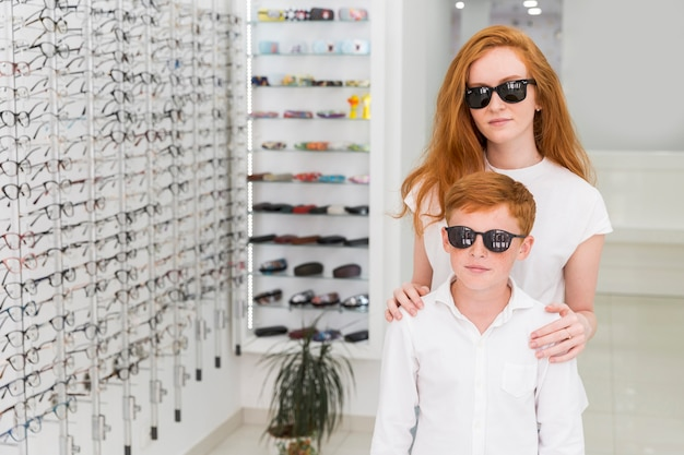 Brother and sister with black eyeglasses standing together in optics shop Free Photo