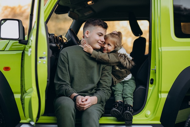 Brother with little sister sitting in green car Free Photo