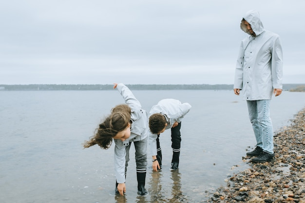Brother with sister have a fun in the sea wearing in raincoat Premium Photo