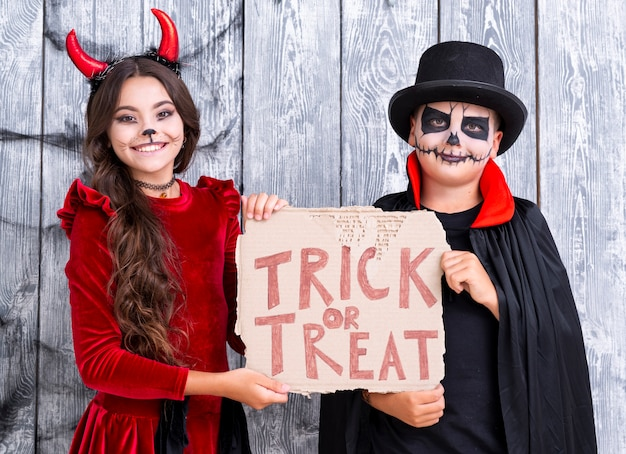 Brothers holding trick or treat sign in halloween costumes Free Photo