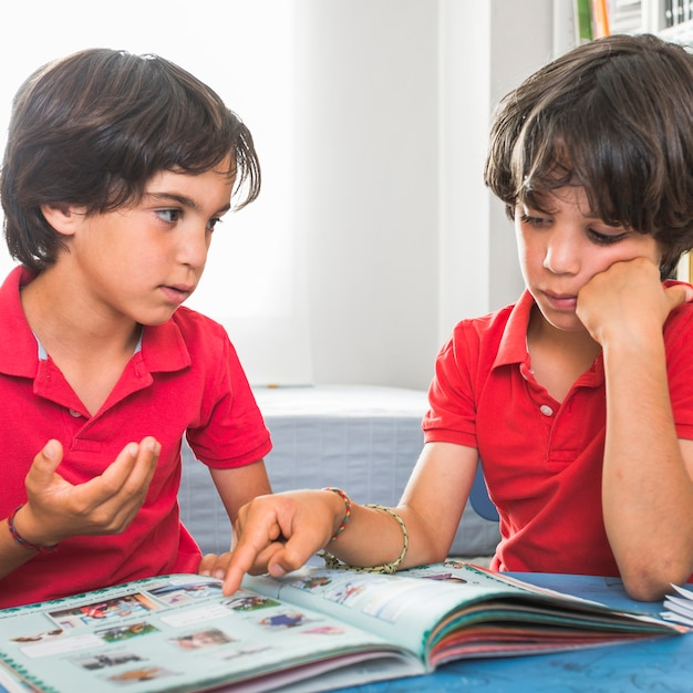 Brothers talking sitting with book Free Photo