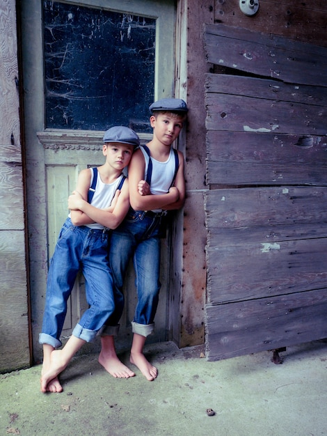 Brothers with suspenders and hats leaning on an old wooden building under the sunlight Free Photo