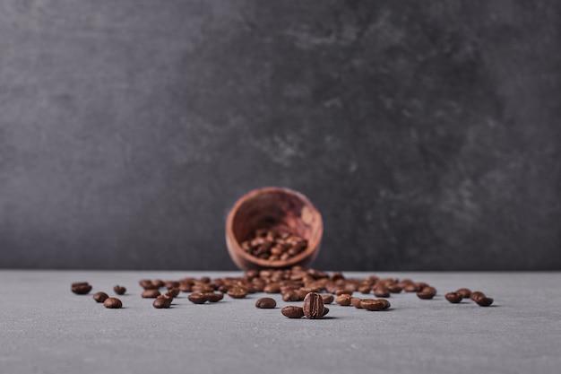 灰色の背景に茶色のアラビカ豆。 無料写真
