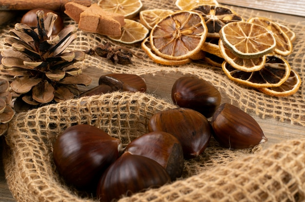 栗、シナモンスティック、ドライレモン、松ぼっくりの上面とフラットレイアウトと茶色の秋の静物 Premium写真