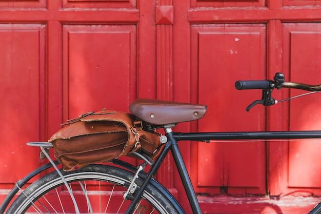 Brown bag on bicycle against closed red door Free Photo