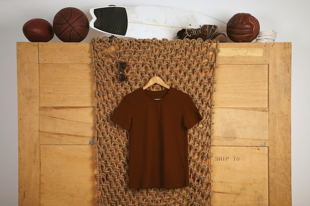 T-shirt in cotone di base marrone presentata in interni rustici con palline da gioco in pelle vintage sulla parte superiore Foto Gratuite