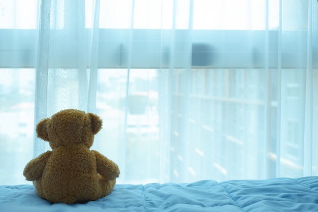 Brown bear doll sitting on the bed and looking thru the curtain and window Premium Photo