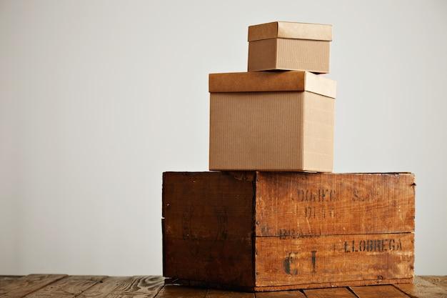 흰색에 고립 된 소박한 나무 테이블 위에 피라미드에 배열 된 다양한 크기와 질감의 갈색 상자 무료 사진