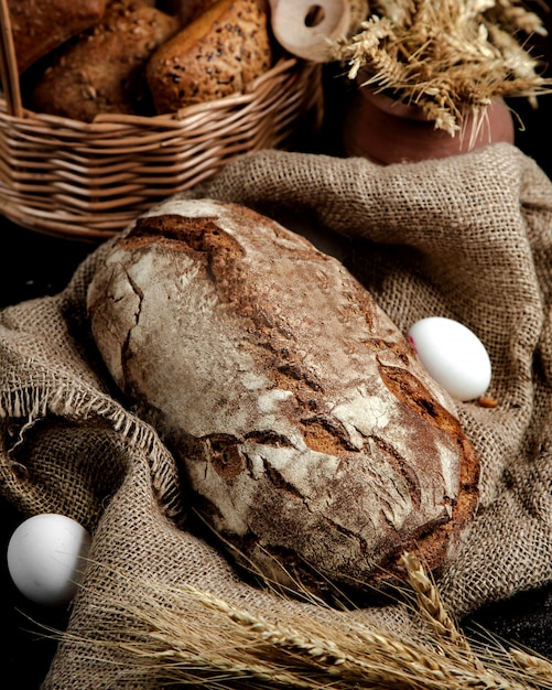 Brown bread loaf served on linen cloth in rustic style Free Photo