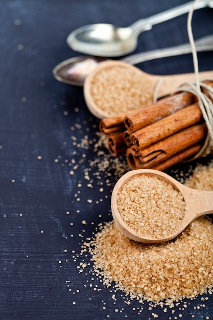 Brown cane sugar, cinnamon sticks and star anise closeup on black board background. Premium Photo