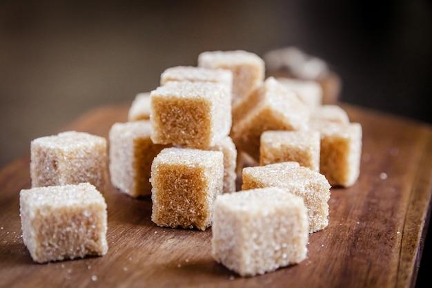 Кубики коричневого тростникового сахара на деревянной разделочной доске Premium Фотографии